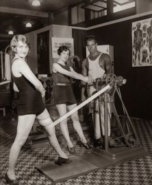 Bodybuilder Charles Atlas (1892 - 1972) demonstrates the Electric Vibrator, an innovative aid to muscle development, to Miss Beth Milton, circa 1930. (Photo by FPG/Hulton Archive/Getty Images)
